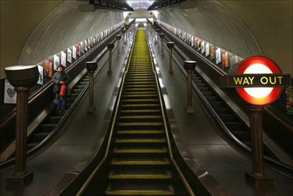A passenger uses the escalator to the platforms at St John's Wood Underground Station, in London.