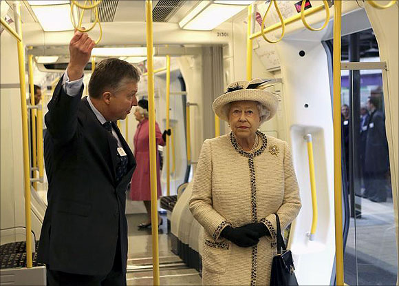 Britain's Queen Elizabeth speaks with a member of staff as she inspects a tube train during her visit to Baker Street underground station in London.