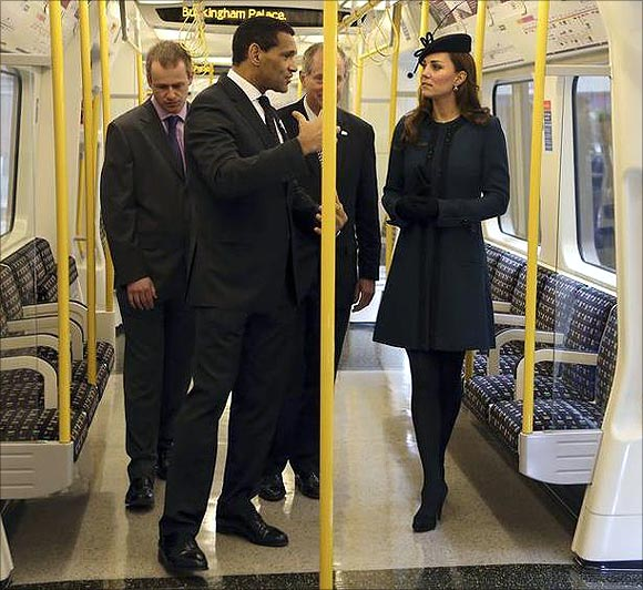 Britain's Catherine, Duchess of Cambridge (R) inspects a tube train during her visit to Baker Street underground station.