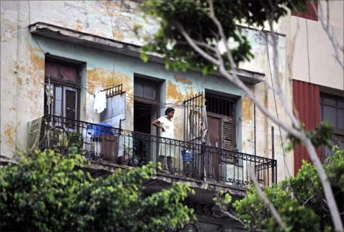 A woman stands with her child on the balcony of her apartment in Havana.