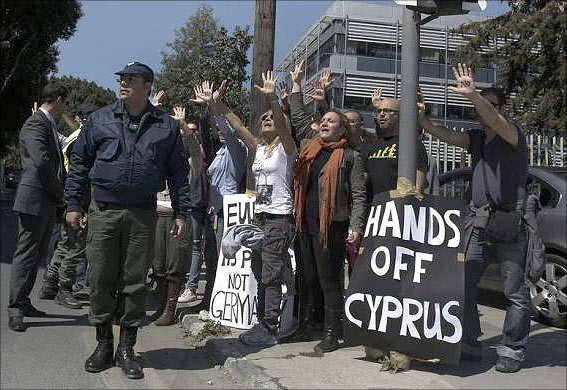 Demonstrators raise their arms in protest as Cypriot President Nicos Anastasiades's convoy drives to the parliament in Nicosia.