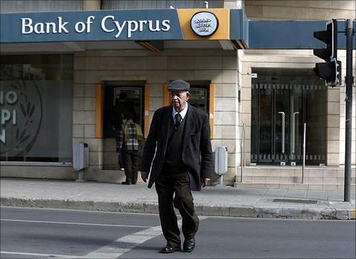 An elderly man crosses the street in front of a branch of the Bank of Cyprus in Nicosia.