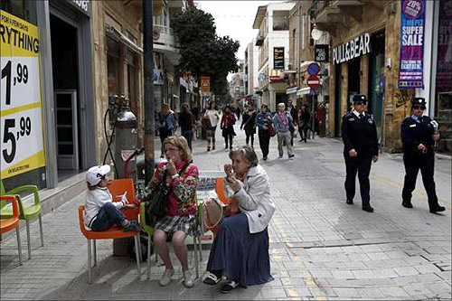 Two Cypriot policewomen patrol at a main market street of capital Nicosia.