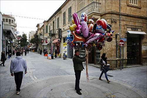 A man selling ballons stands in the middle of the market Ledras street in Nicosia.