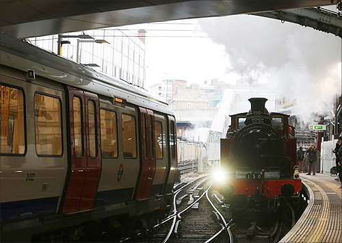 A steam train passes a tube train as it enters Farringdon Station in London.