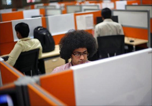 Employees work at their desks inside Tech Mahindra office building in Noida.
