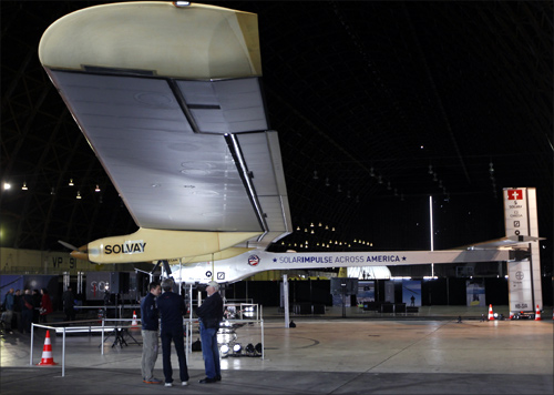 People stand below a wing on the Solar Impulse at Moffett Field in Mountain View, California.