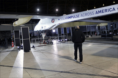 A man walks below a wing on the Solar Impulse at Moffett Field in Mountain View, California.