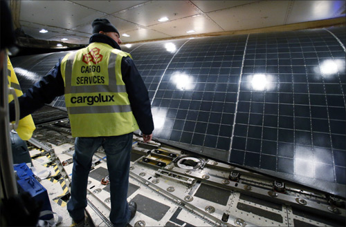 A worker loads the wings of the Solar Impulse aircraft into a Cargolux Boeing 747 cargo aircraft at Payerne airport.