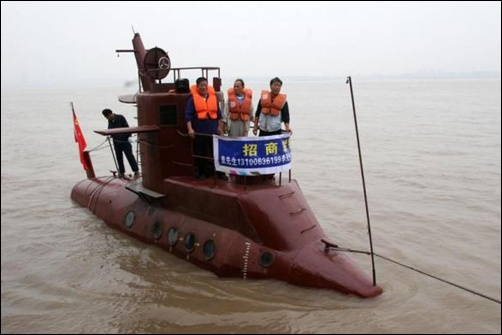 Chinese shipbuilders stand on a submarine designed by a farmer Li Yuming (not pictured) on the Yangtse River in Wuhan, central China's Hubei province.