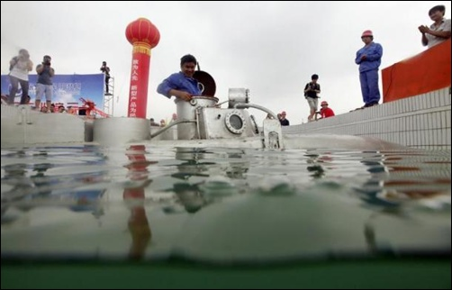 Zhang Wuyi sits in his double-seater submarine before taking it underwater during a test operation at an artificial pool near a shipyard in Wuhan, Hubei province.