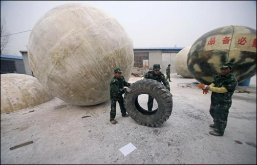 Workers move a tyre near spherical pods named Noah's Ark, designed by Chinese inventor Liu Qiyuan in Xianghe, Hebei province.