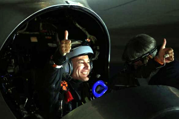 Solar Impulse pilot Bertrand Piccard gestures from the cockpit before taking off from Moffett Field to begin the first leg of his 2013 Across America Mission in Mountain View, California.