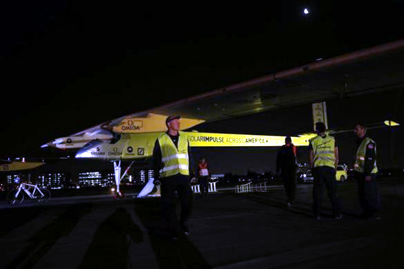 Solar Impulse crew members stand next to their sun-powered aircraft on the runway at Moffett Field before the first leg of its 2013 Across America Mission, piloted by Bertrand Piccard, in Mountain View, California.