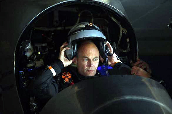 Solar Impulse pilot Bertrand Piccard puts on his flight helmet before taking off from Moffett Field to begin the first leg of his 2013 Across America Mission in Mountain View, California.