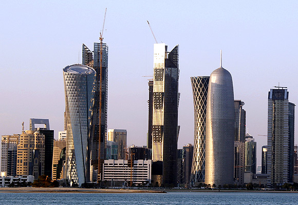 Sun reflects off the glass and steel buildings on the Doha skyline.