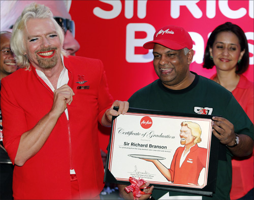 AirAsia's Chief Executive Tony Fernandes (R) presents a certificate to British entrepreneur Richard Branson.