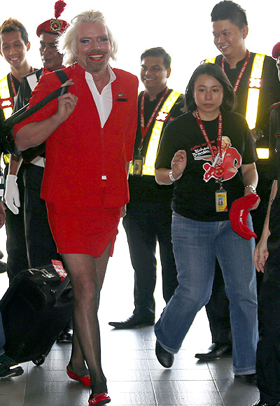 British entrepreneur Richard Branson, wearing an AirAsia stewardess uniform, speaks during an AirAsia promotional event after arriving at an airport in Sepang, outside Kuala Lumpur.