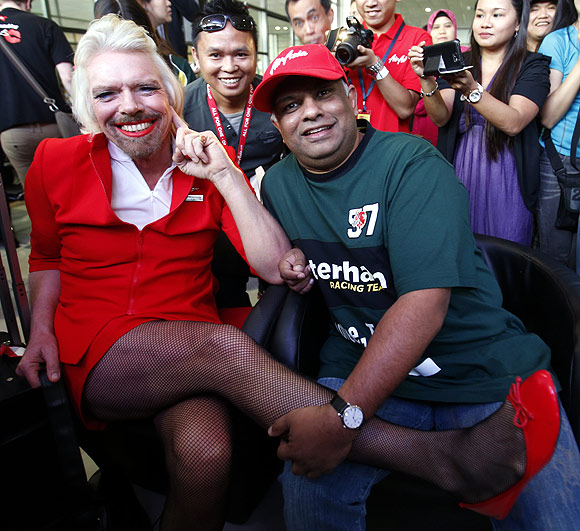 British entrepreneur Richard Branson (L), wearing an AirAsia stewardess uniform, shows his shaved leg, as AirAsia's Chief Executive Tony Fernandes (R) looks on.