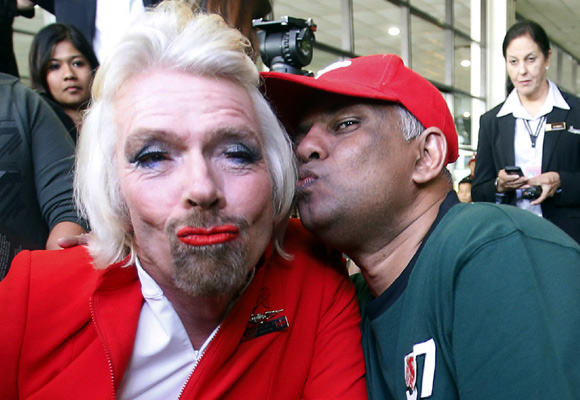 AirAsia's Chief Executive Tony Fernandes pretends to kiss British entrepreneur Richard Branson (L).