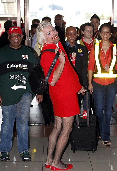 Richard Branson (C), wearing an AirAsia stewardess uniform, poses as AirAsia's Chief Executive Tony Fernandes (L).