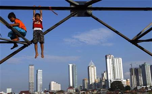 Children play at an electricity pylon in Jakarta.