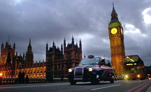 A bus and taxi pass Big Ben on Westminster Bridge in London.