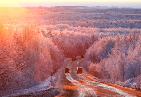 Vehicles drive during sunrise in the Taiga area along the M54 Krasnoyarsk   Mongolia highway, south of Russia's Siberian city of Krasnoyarsk.
