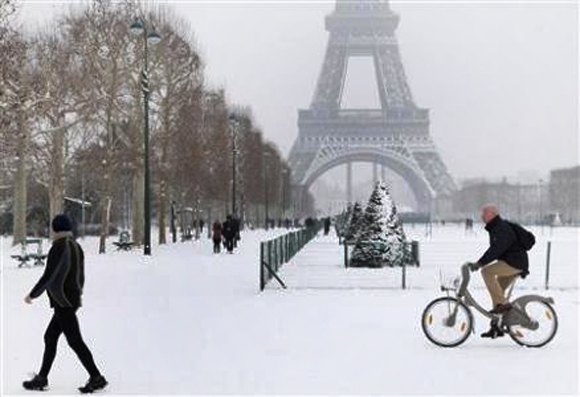 A man rides a Velib self-service public bicycle as he makes his way along a snow-covered area at the Champs de Mars near the Eiffel Tower in Paris.