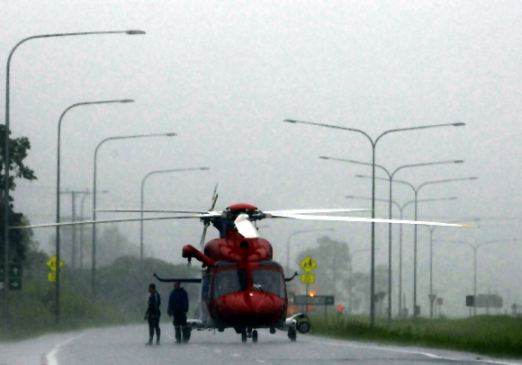 A helicopter blocks the road to traffic, due to flooding, on the highway to Toowoomba, 80 km (50 miles) southeast of Brisbane.