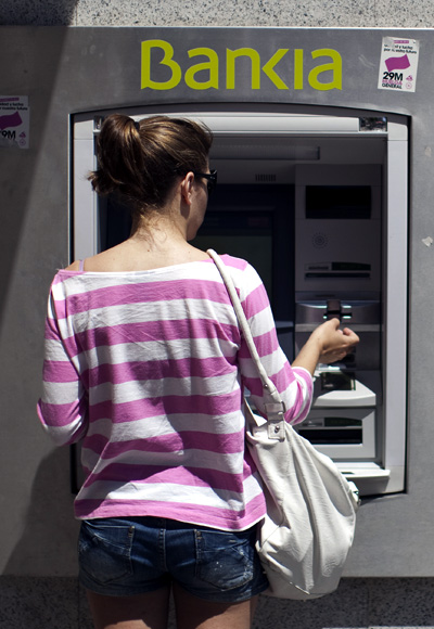 A woman uses a Bankia bank automated teller machine (ATM).