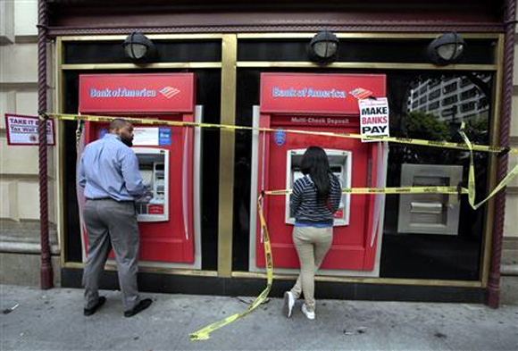 People use ATM machines at a Bank of America branch after it was occupied during a ''Make Wall Street Banks Pay'' protest march in Los Angeles, California.