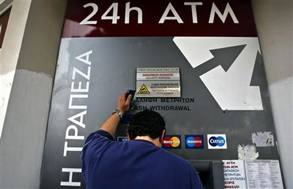 A man makes a transaction at an ATM outside a branch of Laiki Bank in Nicosia.