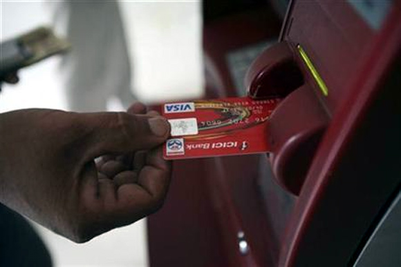 A customer uses his card to withdraw money from an ATM in Jammu.