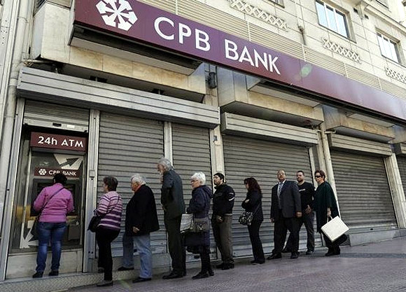 People queue up to make a transaction at an ATM machine outside a closed Cyprus Popular Bank (CPB) branch in Athens.