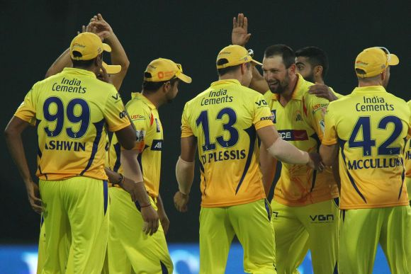 Chennai Super Kings players celebrate at the fall of a wicket