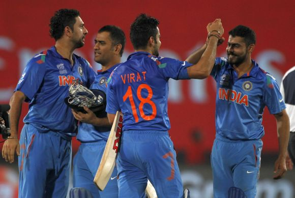 Mahendra Singh Dhoni celebrates with teammates after India beat South Africa in the second semi-final of the World T20