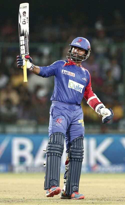 Dinesh Karthik raises his bat after his half-century