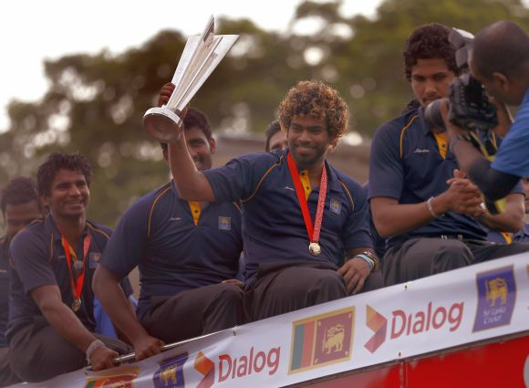 Sri Lanka's Twenty20 cricket captain Lasith Malinga (2nd R) shows the 2014 T20 trophy after they arrived at the Bandaranaike International Airport