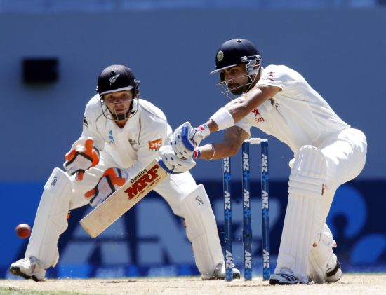 Virat Kohli plays a shot as BJ Watling looks on