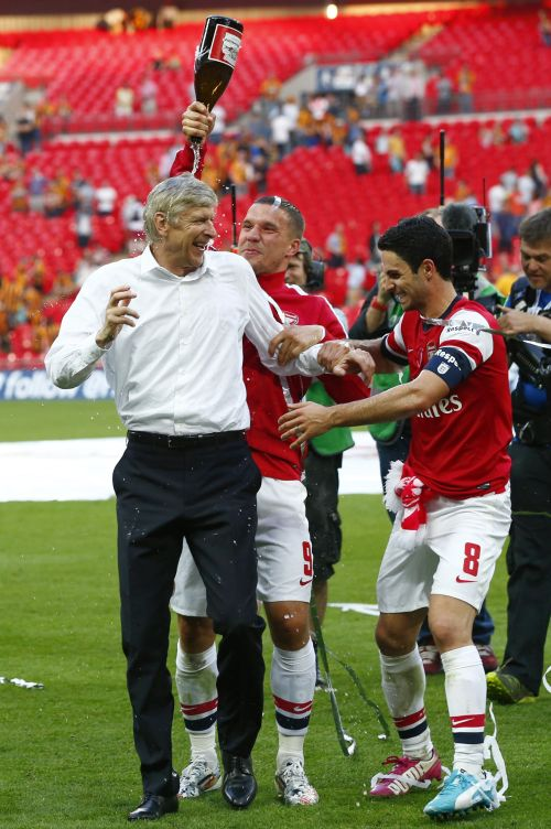 Arsenal manager Arsene Wenger (L), is covered in champagne by his players Lukas Podolski (C) and Mikel Arteta as they celebrate their victory against Hull City in the FA Cup final