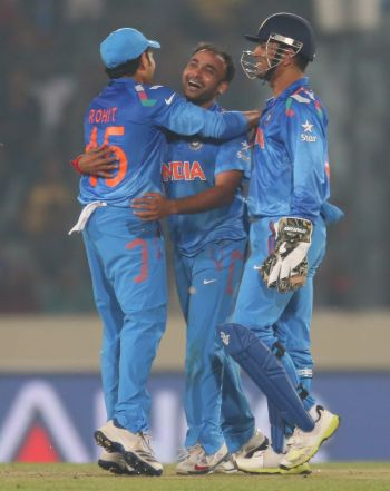 Amit Mishra is congratulated by Rohit Sharma and Mahendra Singh Dhoni
