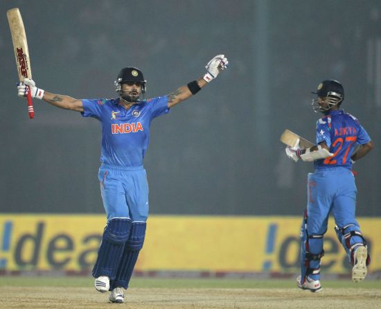 India's captain Virat Kohli celebrates after scoring a century as Ajinkya Rahane (R) watches during their Asia Cup 2014 match against Bangladesh