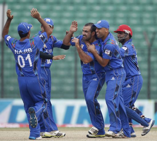 Afghanistan's fielders congratulate bowler Samiullah Shenwari (C) after he dismissed Pakistan's Sohaib Maqsood