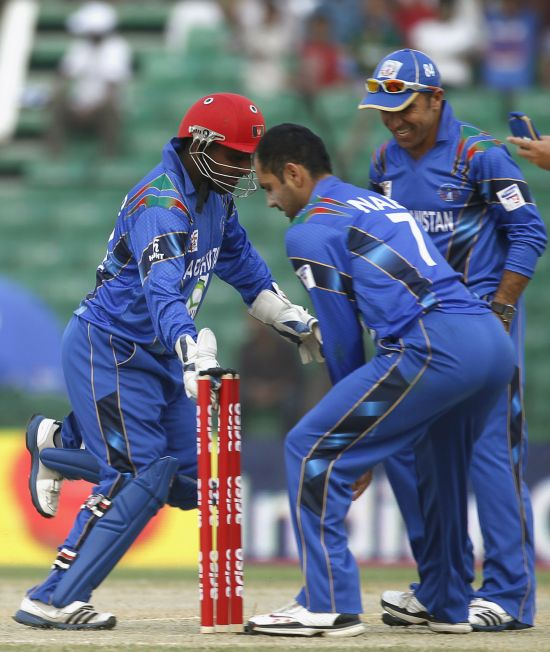Afghanistan's wicketkeeper Mohammad Shahzad (L) breaks the wicket with Najibullah Zadran (R) to dismiss Pakistan's captain Misbah-ul-Haq