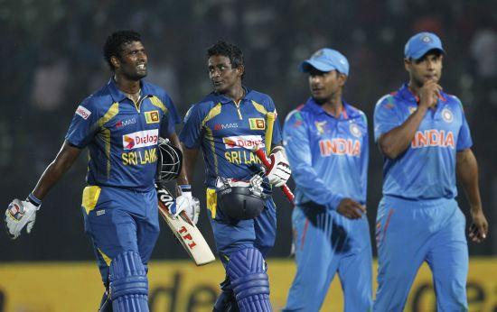 Sri Lanka's Thisara Perera and Ajantha Mendis walk back to the pavillion after winning the match
