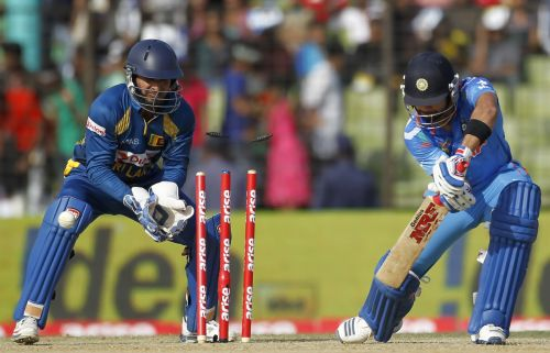Virat Kohli is bowled out as Sri Lanka's wicketkeeper Kumar Sangakkara (L) watches on