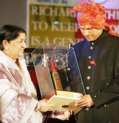 Lata Mangeshkar presents a golden bat to Sachin Tendulkar
