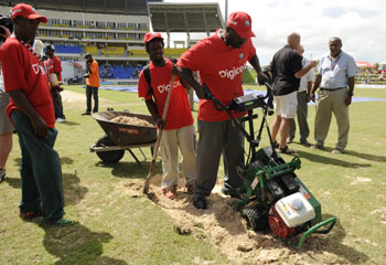 Groundsman dig up the bowler's run up at the Sir Vivian Richards stadium