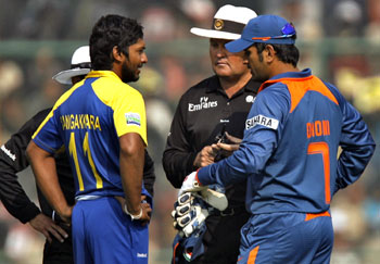 Kumar Sangakkara and M S Dhoni in discussion with the umpires